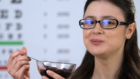 Happy female wearing eyeglasses eating bilberry, vitamins for healthy vision. Stock footage stock video