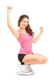Happy female on a weight scale Royalty Free Stock Photos