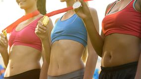 Happy female winners showing medals, posing for photos at awarding ceremony stock photos
