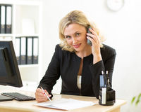 Happy female worker businesswoman talking phone in office Royalty Free Stock Photo