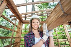 Happy Female Worker Carrying Wooden Planks Stock Photography