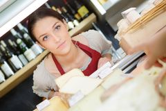 Happy female worker slicing cheese with knife in shop. Female Royalty Free Stock Images