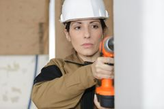 Happy female worker using battery drill in wall. Happy female worker using a battery drill in a wall Royalty Free Stock Image