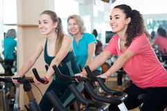 Happy females of different age training on exercise bikes Stock Photo