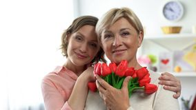 Happy females looking at camera holding tulip flowers, international womans day. Stock photo stock photo