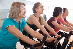 Happy females riding stationary bicycles. In modern gym for women Stock Photo