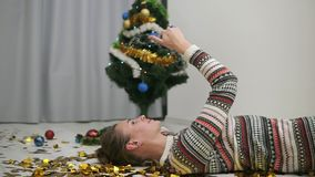 Happy festive girl laying on the floor in gold glitter confetti and taking selfie. Decorated christmas tree on the. Background stock footage
