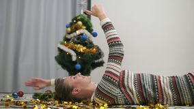 Happy festive girl laying on the floor in gold glitter confetti and taking selfie sending kiss. Decorated christmas tree. On the background stock video