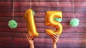 Happy fifteen birthday, golden air balloons with number 15, anniversary celebration with decorations