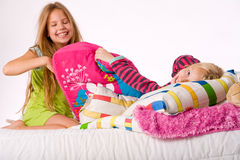 Happy when fighting. Two young children enjoying their colorful bed royalty free stock photography