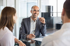Happy financial agent smiling. Mature financial agent in meeting sitting with young couple. Happy consultant talking with couple about their savings plan Royalty Free Stock Images