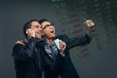 Happy financial brokers. Looking at the electronic stock exchange board Royalty Free Stock Photography