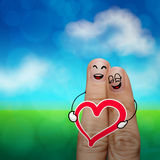 The happy finger couple in love with painted smiley. And hold heart on nature background Royalty Free Stock Image