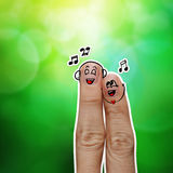 The happy finger couple in love with painted smiley. And sing a song on green nature background Stock Photo