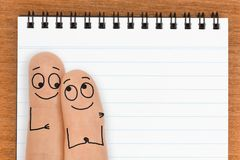 Happy Finger Face Couple with Blank Notepad Copy Space Stock Images