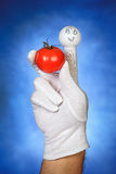 Happy finger puppet holding tomato fruit Royalty Free Stock Photo