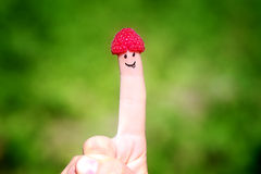Happy finger with raspberries and painted smiles Royalty Free Stock Photo