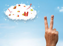 Happy finger smiley with graph cloud icons in the sky. Happy finger smiley faces on hand with graph cloud icons in the sky royalty free stock image