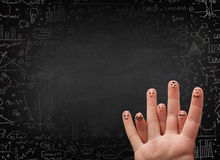 Happy finger smileys with black chalkboard in background Stock Image