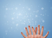 Happy finger smileys with empty blue bokeh background Stock Photography