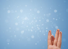 Happy finger smileys with empty blue bokeh background