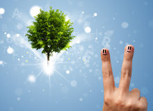 Happy finger smileys with green magical glowing tree Royalty Free Stock Photo