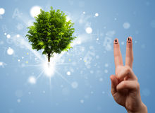 Happy finger smileys with green magical glowing tree Stock Photos