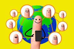Happy finger using mobile phone with world map, Social network c Stock Photography