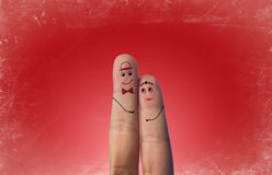 Happy Fingers Couple In Love With Painted Smiley. On red vintage background royalty free stock photo