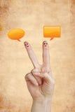 Happy fingers with speech bubbles on blackboard Stock Photo