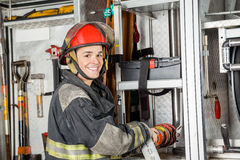 Happy Firefighter Fixing Water Hose In Truck Stock Image