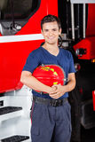 Happy Firefighter Holding Helmet At Fire Station Stock Photo