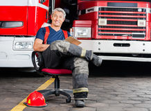 Happy Firefighter Sitting On Chair Against Trucks Royalty Free Stock Photos