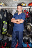 Happy Firefighter Standing At Fire Station. Portrait of happy firefighter standing arms crossed at fire station Stock Photos
