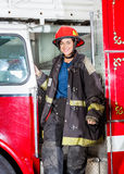 Happy Firefighter In Uniform Standing On Truck. Portrait of happy female firefighter in uniform standing on truck at fire station stock photography