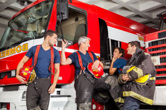 Happy Firefighters Conversing While Leaning On Royalty Free Stock Photography