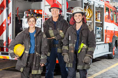 Happy Firefighters Standing Against Truck. Portrait of happy firefighters standing together against truck at fire station Stock Photography