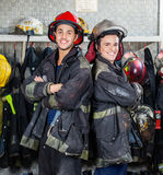 Happy Firefighters Standing Arms Crossed. Portrait of happy firefighters standing arms crossed at fire station Royalty Free Stock Image
