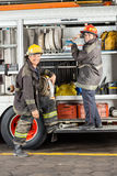 Happy Firefighters Standing By Truck At Fire Station Stock Images