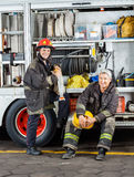 Happy Firefighters By Truck At Fire Station. Portrait of happy male firefighters by truck at fire station Royalty Free Stock Photography