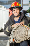 Happy Fireman Holding Hose At Fire Station Stock Images