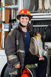 Happy Fireman Holding Hose While Standing By Truck Royalty Free Stock Photos