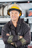 Happy Fireman Standing At Fire Station. Portrait of happy mature fireman standing arms crossed at fire station Royalty Free Stock Images