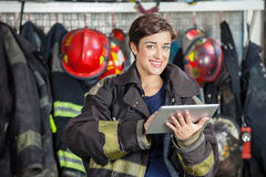 Happy Firewoman Holding Digital Tablet At Fire Royalty Free Stock Photography