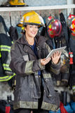Happy Firewoman Holding Digital Tablet At Fire Stock Photography