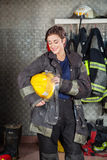 Happy Firewoman Holding Helmet Stock Photos