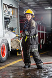 Happy Firewoman Spraying Water During Practice. Portrait of happy firewoman spraying water during practice at fire station Royalty Free Stock Photo