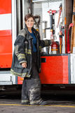 Happy Firewoman Standing By Truck At Fire Station Stock Image