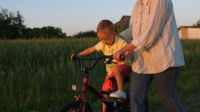Happy first ride of little boy on bike with granny stock video footage