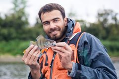 Happy Fisher. Mid adult fisherman on holidays on river, relaxing and fishing trout. Focus on fisher Royalty Free Stock Images